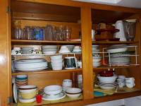Contents of cabinets above sink area includes set of Corelle dishware - some pottery ware - glassware Etc.