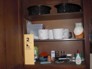 Cupboard contents: (3) shelves of mugs, roasters, kitchen items